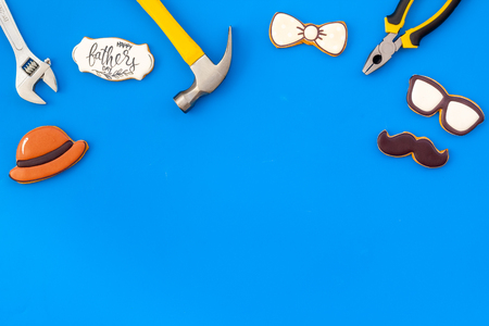 Moustache, hat, glasses, bow tie, set of tools and cookie with copy for Happy Father Day celebration party on blue background top view copy space