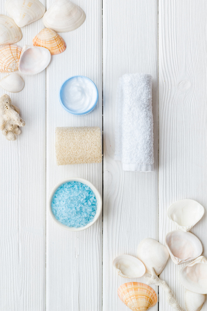 Skin care concept. Cosmetics with Dead Sea minerals. Cream, lotion, salt, soap and shells on white wooden table background top view Archivio Fotografico - 121245689