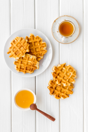 Traditional Belgian waffles with honey and tea on served white wooden table  top view Zdjęcie Seryjne