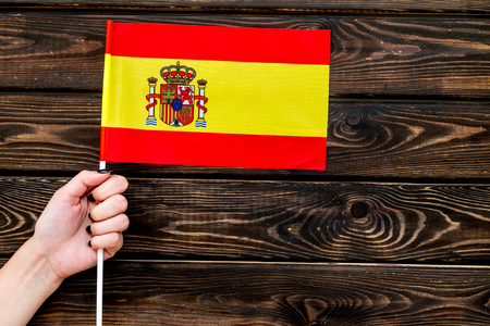 Flag of Spain in hand on wooden top view.