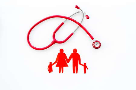 Family doctor. Cardiologist. Diagnostic and cure of cardiac disease with stethoscope and family paper figures on white  top view