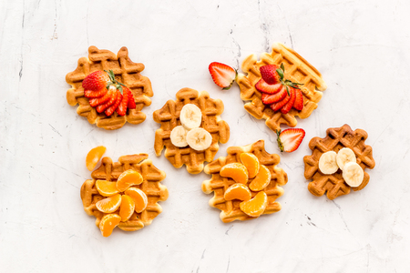 Sweet breakfast. Homemade Viennese waffles with strawberry, tangerine and banana toppings on white  top view 版權商用圖片