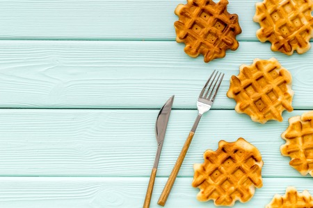 Hot homemade breakfast. Traditional belgian waffles on served mint green wooden table  top view mockup 免版税图像