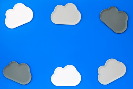 Cloud service concept with clouds figures on blue office desk  top view mockup