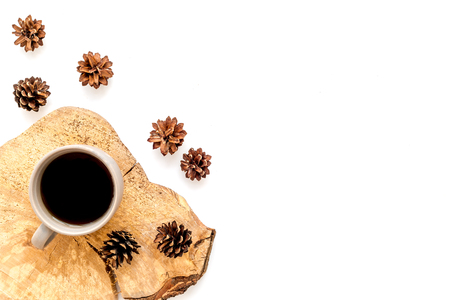Cup of coffee on wooden sawcut and pine cone pattern for blog title on white  top view mock up