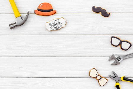Mustache, hat, glasses, bow tie, set of tools and cookie with copy for Happy Father Day celebration party on white wooden  top view copy space 免版税图像