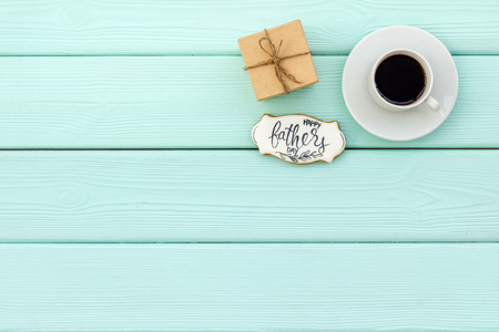 Cup of black coffee, box with gift and copy for Happy Father Day celebration party on mint green wooden top view copy space