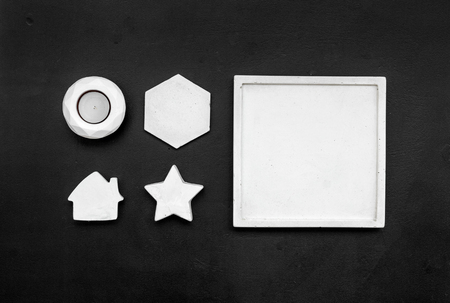 Candle, concrete figures and tray decorations for modern home office design on black work desk  flat lay mock up 版權商用圖片