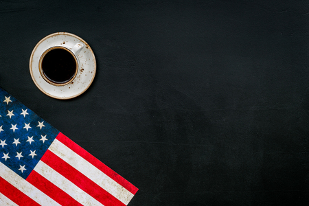 Independence day of USA with flag and cup of coffee on black background top view space for text
