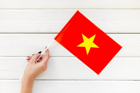 Independence Day of Vietnam concept with flag in hand on white wooden background top view.