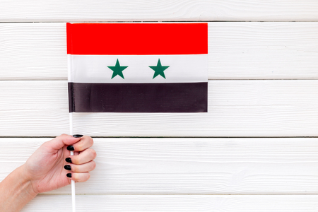 Independence Day of Syria concept with flag in hand on white wooden background top view Stockfoto