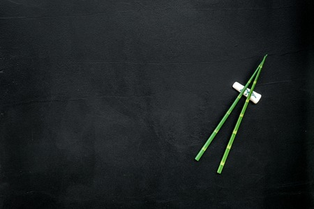 Oriental table set up with bamboo sticks on black background top view space for text