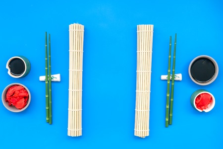 Oriental table set up with bamboo sticks for sushi and maki, soy sauce on blue background top view