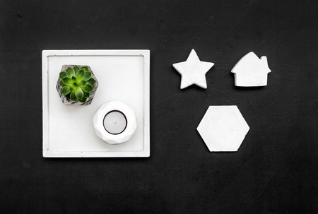 Plant, candle, concrete figures and tray decorations for modern home office on black background flat lay