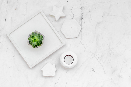 Work desk design with concrete decorations, candle and plant on marble background top view space for text