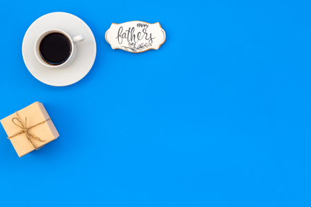 Cup of coffee, gift and copy for Happy Father Day party on blue background top view copy space Stock Photo