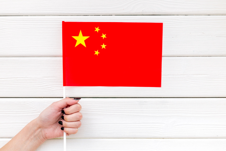 Symbol of the national day of China concept with flag in hand on white wooden background top view