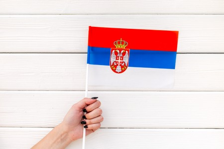 Symbol of the national day of Serbia concept with flag in hand on white wooden background top view Imagens