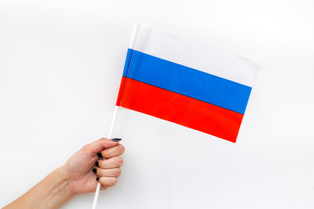 Flag of Russia in hand on white background top view
