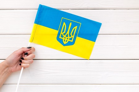 Independence Day of Ukraine concept with flag in hand on white wooden background top view