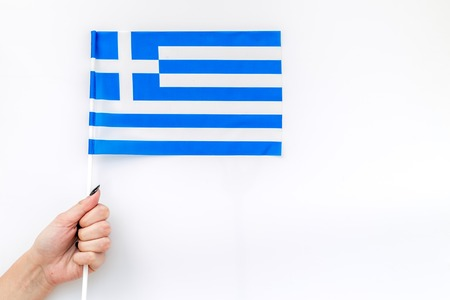 Flag of Greece in hand white background top view Reklamní fotografie