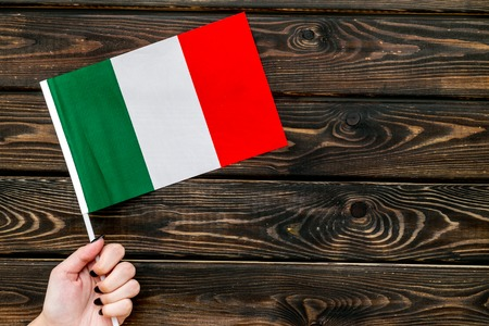 National day of Italy concept with flag in hand on wooden background top view