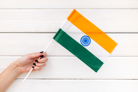 National day of India concept with flag in hand on white wooden background top view