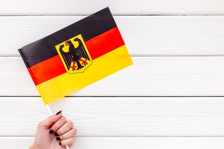 Independence Day of Germany concept with flag in hand on white wooden background top view