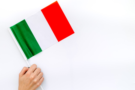 Independence Day of Italy concept with flag in hand on white background top view