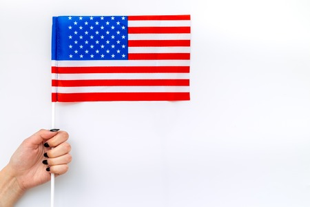 Flag of USA in hand on white background top view