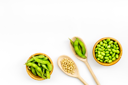 vegan food with green soybeans or edamame in spoon and bowl on white background top view copy space