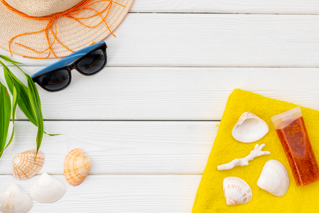 Summer travaling to the sea with straw hat, sun glasses, sunblock lotion on white wooden background top view mock up Archivio Fotografico