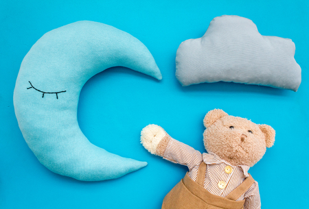 Put baby into bed with moon pillow, clouds, teddy bear and toy on blue background top view Banque d'images