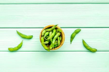 vegan food with green soybeans or edamame on mint green wooden background top view