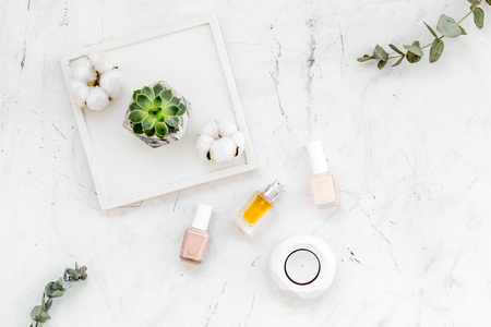 modern design of work desk with nail polish and perfume on white marble background top view