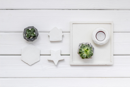 Work desk design with concrete decorations, candle and plant on white wooden background top view