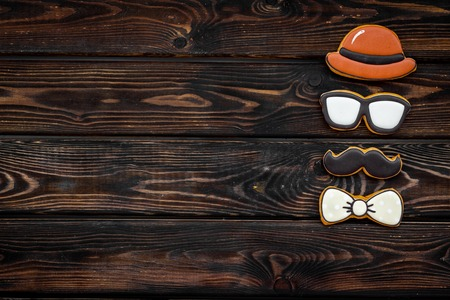 Happy Father Day celebration with cookies in shape of bow tie, moustache, glasses and hat on wooden background top view mockup