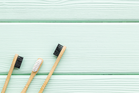 Zero waste lifestyle concept. Dental care with eco friendly bamboo tooth brush on mint green wooden background top view space for text