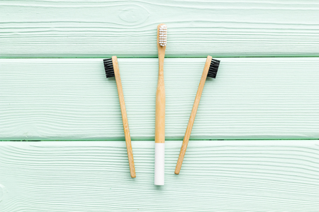Zero waste lifestyle concept. Dental care with eco friendly bamboo tooth brush on mint green wooden background top view
