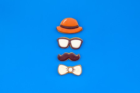 Hat, moustache, glasses, bow tie figures. Design for Father Day celebration party with cookies on blue background top view mockup.