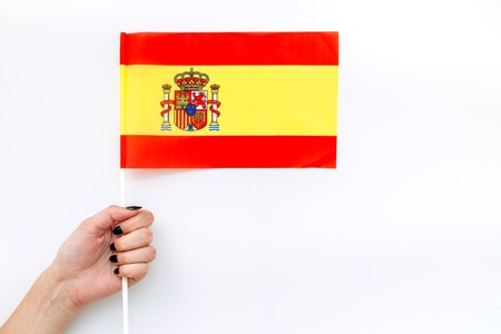 Symbol of the national day of Spain concept with flag in hand on white background top view