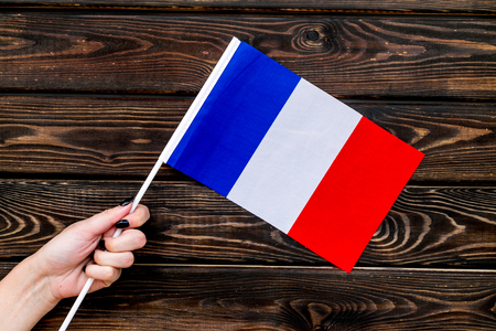 Independence Day of France concept with flag in hand on wooden background top view.
