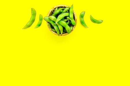 Vegan food concept with green soybeans or edamame on yellow desk background top view copy space Stock Photo