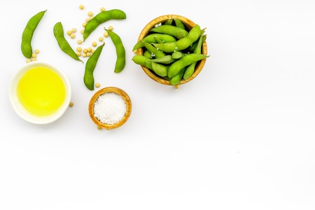 Ingredients. Green soybeans or edamame and oil for fresh healthy organic food on white background top view space for text