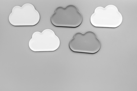 Share information on the Internet. Clouds figures for cloud storage on gray office background top view mockup 写真素材