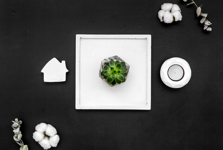 Home decoration. Modern design of work desk with candle, plant, house figure on black background top view