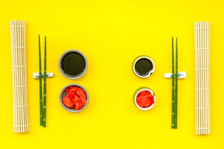 Oriental table set up. Japanese food cooking set with soy sauce, ginger, bamboo sticks for sushi or maki on yellow background top view
