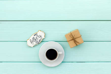 Happy Father Day celebration with gift and cup of coffee on mint green wooden background top view mockup Stock Photo