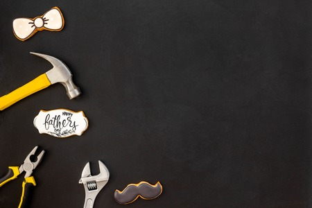 Moustache, bow tie figures, instruments for repairing house. Design for Father Day celebration party with cookies, gift box and coffee on black background top view mock up