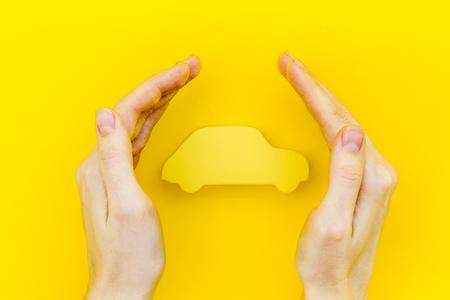 Concept d'achat et d'assurance de voiture avec la figure de voiture dans les mains sur la vue de dessus de fond de bureau jaune